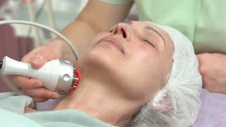 Rf skin tightening procedure. Mature woman, hand of cosmetologist. Health, beauty and rejuvenation.