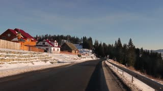Road through the village to the mountains. Wonderful winter sunny day. Beautiful rural mountain home.