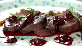 Roasted veal with cherry sauce. Meat dish macro.