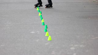 Roller skating training with agility markers. Crossover tricks with roller skates. Close up.