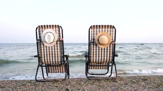 Romantic concept, two chaise lounges on the seashore. Sea, sand, evening sky and straw hats. Back rear view.
