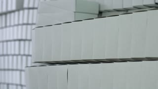 Row of white blank boxes. Lots of empty paper boxes. Packages for food products. Disposable containers in warehouse.