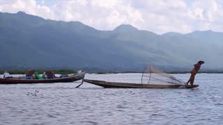 Rowing of paddle with leg. Fisherman floating on a boat on Inle Lake.