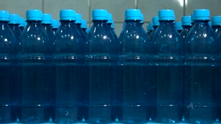 Rows of water bottles. Side view of bottles. Raise profit by improving quality. Cleanliness means perfection.