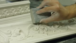 Rubbing gypsum with emery. Polishing a painting frame. Expensive picture frame. The perfect condition of ornament.