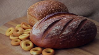 Rye and wheat bread with sesame seeds and bagels on a wooden background