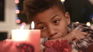 Sad boy looking at candle. Upset boy near Christmas candle. Moment of sadness. Young man's deep emotion.