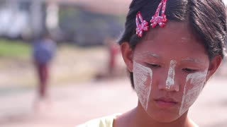 Sad face of young asian girl. Socially disadvantaged children. Burmese cosmetics on the face of the girl. Cheeks anointed with clay.