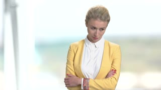 Sad mature business woman. Portrait of frustrated lady in yellow suit. Bright blurred office background.