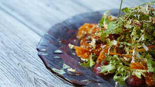 Salad with fish and greens. Salad plate on wooden background. Healthy dish from european cuisine. Juicy salmon and carrot.