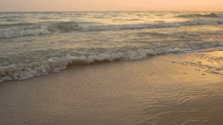 Sandy seashore and waves. Water and sunset sky. Escape from all worries