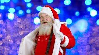 Santa dancing on bokeh background. Cheerful Santa Claus.
