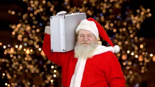 Santa holding a briefcase. Santa Claus on lights background. The job of bringing happiness.