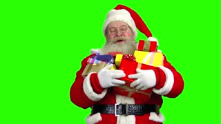 Santa holding presents, green screen. Santa Claus is laughing.
