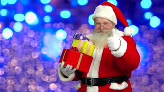 Santa showing thumb up, presents. Santa Claus, bright lights background. Approved by Santa.