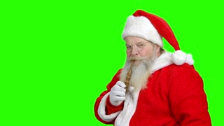 Santa's enjoying smoking the pipe. Green hromakey background.