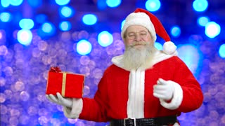 Santa's pointing at the christmas gift. Flashing lights in the blue background.