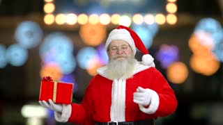 Santa's smiling and pointing at the gift box. Large colorful blured lights in the background.