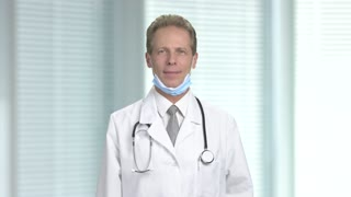 Satisfied doctor with an okay gesture. Smiling mature doctor showing ok sign, blurred background. Human body language.