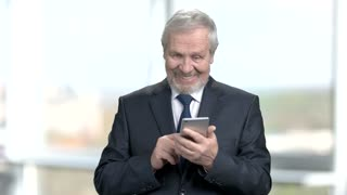 Satisfied elderly businessman with smartphone. Happy senior man in business suit typing a message on blurred background. Older people, business and technology.