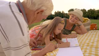 Schoolchild is drawing with colored pencils outdoors. Grandparents looking how granddaughter is drawing, summer nature background. Support of relatives is priceless for skills development of kids.