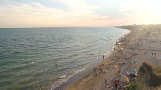 Sea beach and people, summer. Sandy shore, waves and horizon.