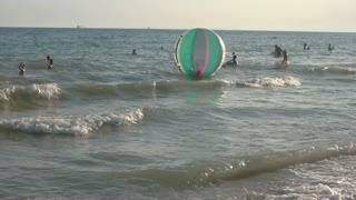 Sea, waves and people. Inflatable water walking ball. Fun vacation ideas.