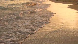 Seashore in slow-mo. Small waves at sunset.