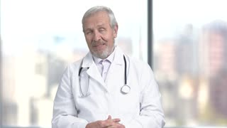 Senior bearded doctor on blurred background. Elderly caucasian doctor is talking and looking at camera. People, professions, medicine.