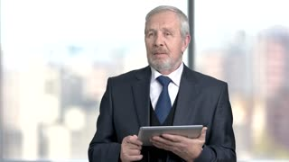 Senior businessman holding pc tablet. Elderly caucasian man in business suit talking at conference using digital tablet. Discussing new project.