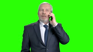 Senior businessman talking on mobile phone. Cheerful bearded man in formal wear talking on cell phone, chroma key background.