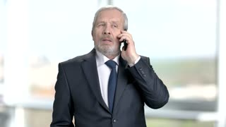 Senior businessman talking on phone. Confident elderly businessman talking on smartphone of blurred background. People, bussiness and communication.