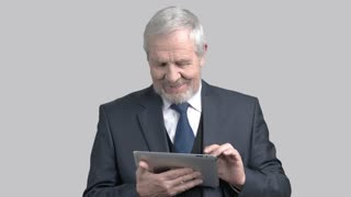 Senior businessman with pc tablet. Elderly man in business suit using digital tablet on grey background.