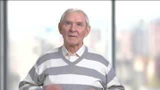 Senior caucasian man having sore throat. Elderly man holding his neck because of throat ache, blurred background.