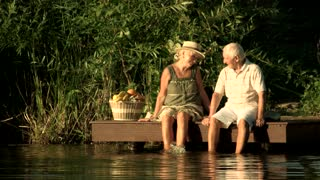Senior couple dangling with legs in river. Beautiful couple of elderly people having fun near water. Family rest on summer nature background.
