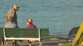 Senior couple on the bench. Elderly people sitting near lake.