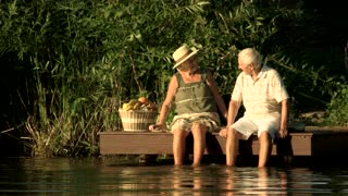 Senior couple sitting near water. Happy elderly man and woman with picnic basket near river. Old couple having rest on nature background.