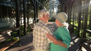 Senior couple smiling and dancing. Man holds woman's hand. We saved love over years. Honesty and support.