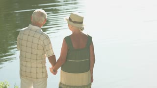 Senior couple standing near lake. Old man indicating with index finger standing near water with wife. Family rest outdoors.
