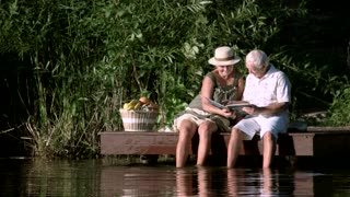 Senior couple with album outdoors. Mature couple relaxing near water with a photo album. Recollection of sweet past.