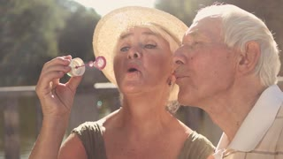 Senior couple with bubble blower. Cute couple of old man and woman blowing soap bubbles together outdoors, slow motion. Leisure and relationhip between elderly people.
