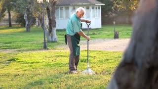 Senior gardener with rake. Old man in apron outdoors. Best gardening tips.
