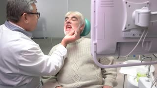 Senior man at the dentist. Dental doctor busy with patient. Qualification and experience.