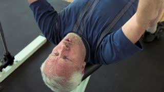 Senior man doing bench press exercise. Male pensioner lifting weight at gym close up. Reasons to strat lifting weights.