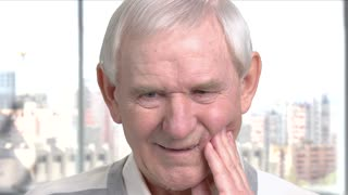 Senior man feeling bad because of toothache. Cheerless elderly man suffering from problem with teeth, window city background.