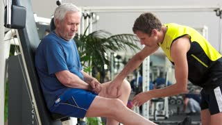 Senior man feeling pain in knee. Fitness trainer massaging injured leg to elderly man at gym. Sport accident concept.
