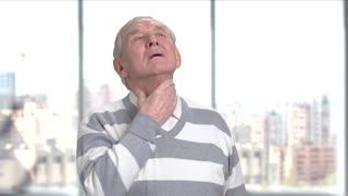 Senior man having ache in throat. Coughing man feeling pain in neck, window city background. Symptoms of flu.