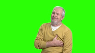 Senior man having heart attack. Older man holds his chest as he suffers from a heart attack, chroma key background.