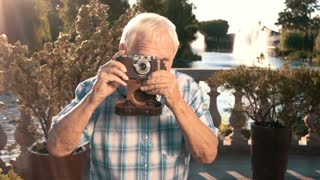 Senior man holding camera. Elderly male outdoors. Grandpa at the resort. Nature inspired photographer.