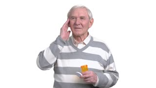 Senior man holding medicine, white background. Older man taking medicine, isolated on white background. Treatment of migraine by pills.